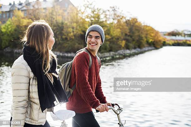 Happy young man with female friend walking by lake during winter