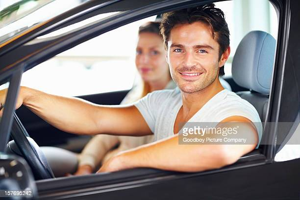 Happy young man with his girlfriend in new car