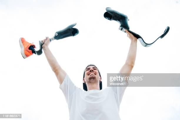 happy young man with leg prosthesis cheering under cloudy sky - membro imagens e fotografias de stock