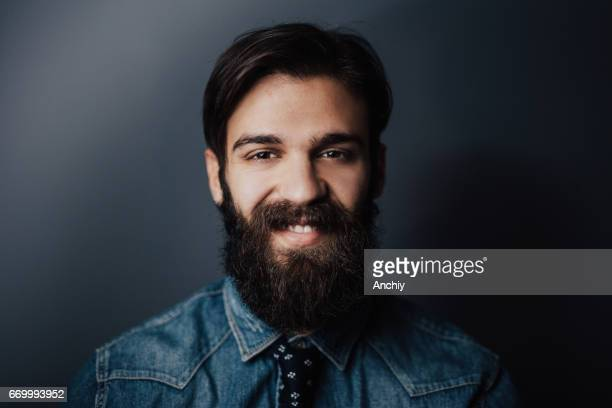 Happy young man with long beard and bright smile