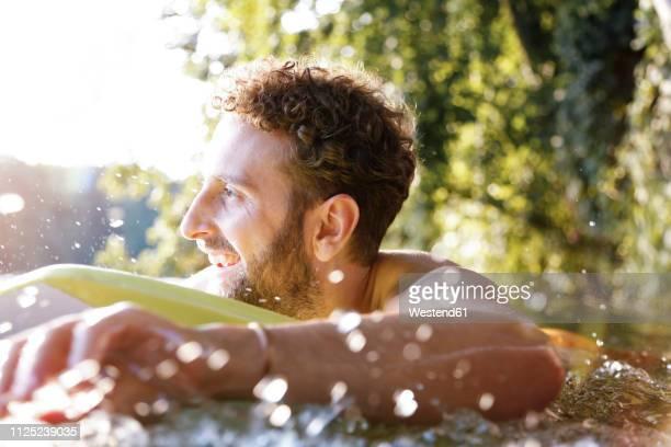 happy young man with surfboard in a lake - nur erwachsene fotos stock-fotos und bilder