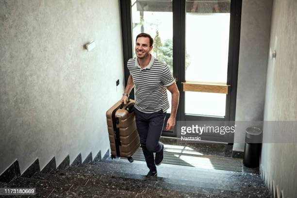 happy young man with travel bag walking inside hotel on a stairs - arrivo foto e immagini stock