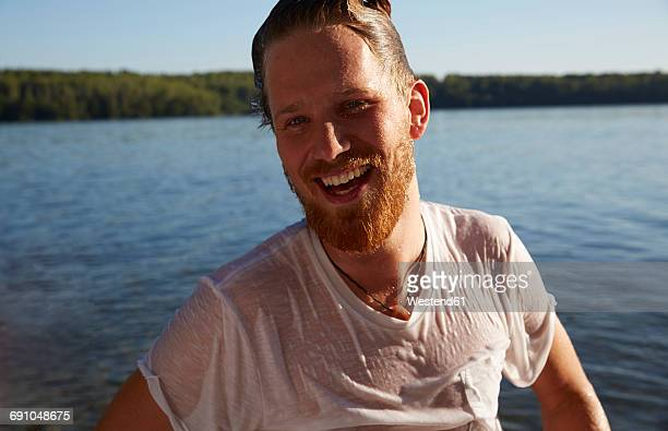 happy young man with wet t-shirt at a lake - wet t shirts fotografías e imágenes de stock