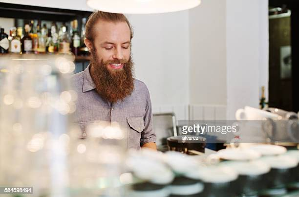 Happy young man working at cafe