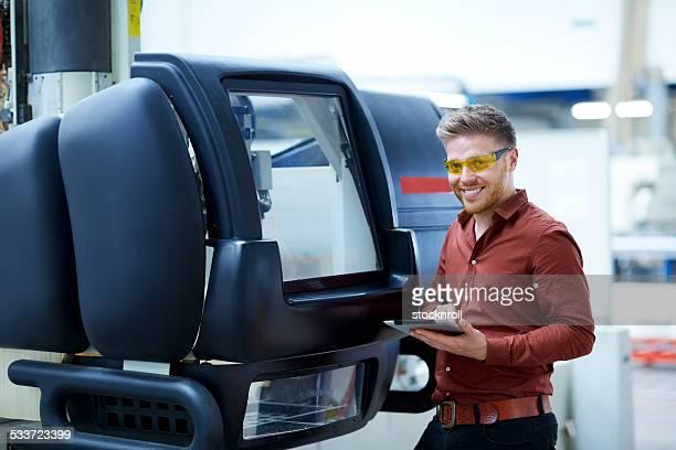 Glückliche junge Mechaniker in Fabrik-workshop