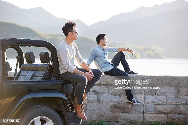 happy young men and jeep - close to stock pictures, royalty-free photos & images