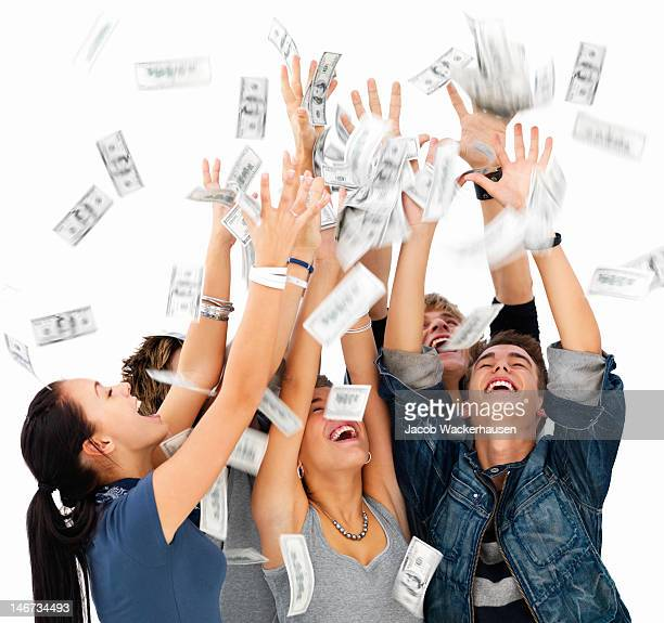 Felices jóvenes hombres y mujeres jugando con dinero