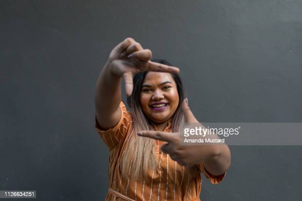 Happy Young Mixed Race Woman Framing her Face with her Hands