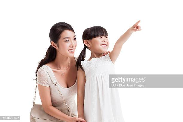 Happy young mother and daughter looking at view