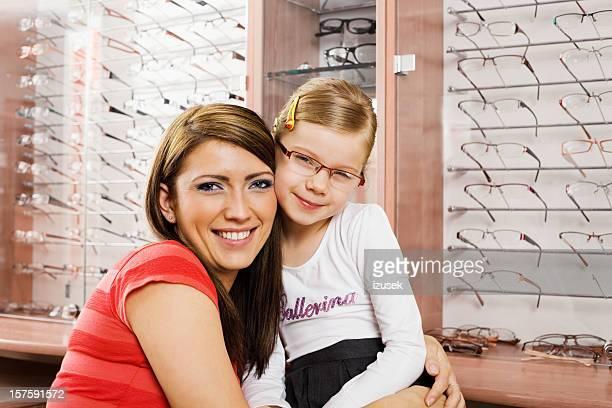 Glückliche junge Mutter und Tochter Einkaufen für neue Brille