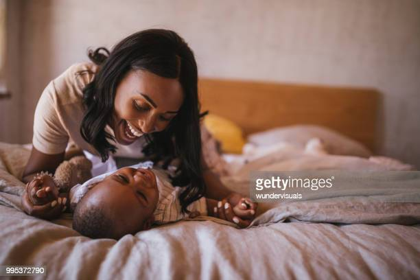 happy young mother and little child playing together in bed - black mothers day stock pictures, royalty-free photos & images
