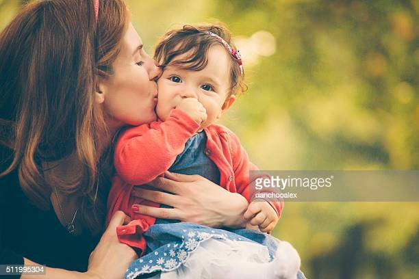 Happy young mother kissing her baby girl