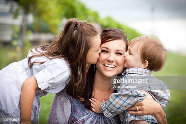 Joven madre feliz, Riendo y Kissed con hija e hijo