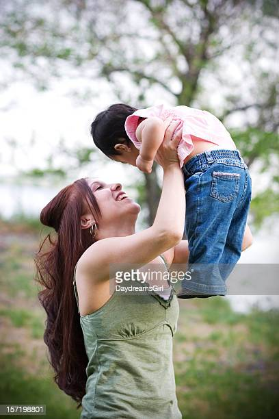 happy young mother lifting baby outdoors in nature - mexican mothers day stock photos and pictures