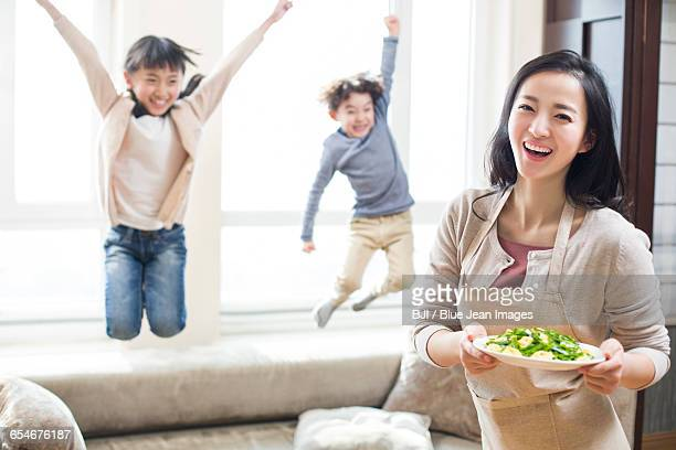 Happy young mother serving food