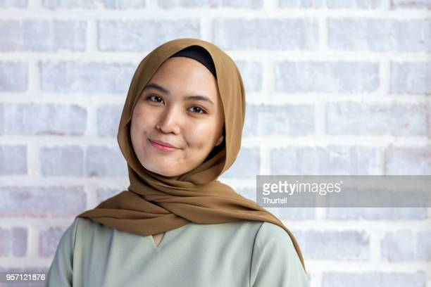 happy young muslim woman smiling wearing hijab - malaysian culture stock pictures, royalty-free photos & images