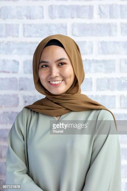 feliz joven mujer musulmana sonriendo llevar hijab - malasia fotografías e imágenes de stock