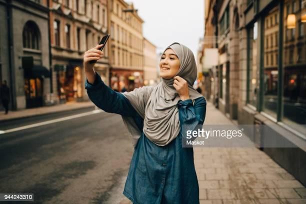 happy young muslim woman taking selfie standing on sidewalk in city - vestimenta religiosa - fotografias e filmes do acervo