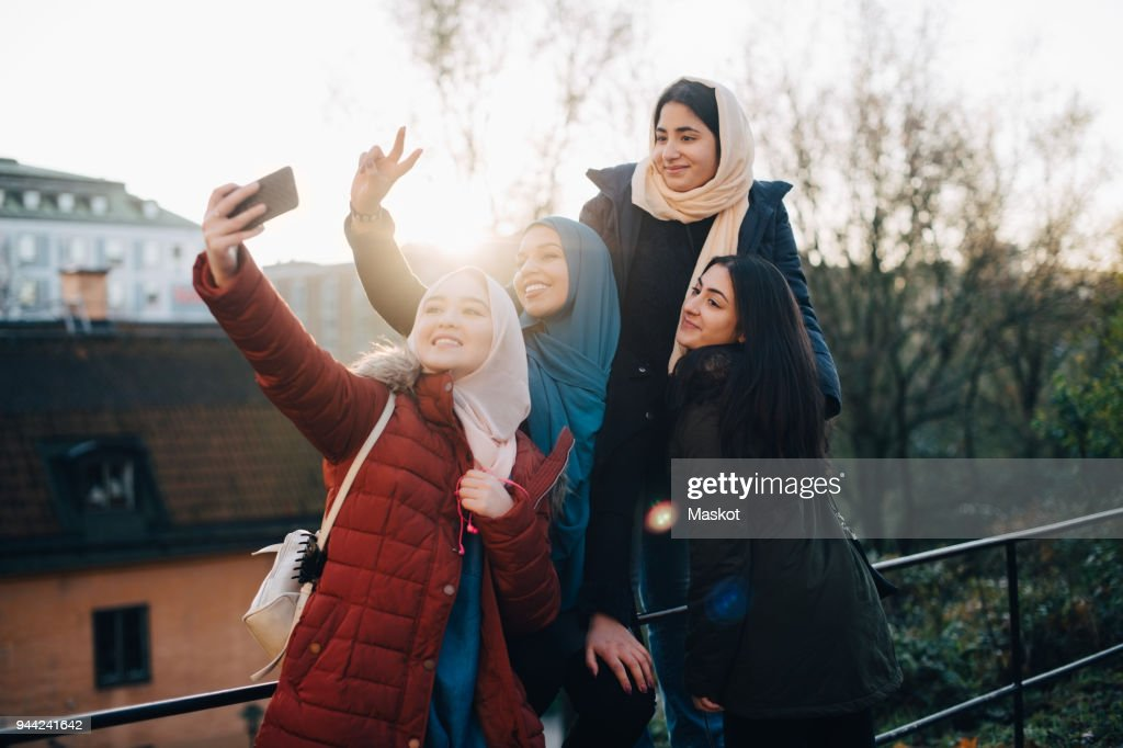 Happy young Muslim woman taking selfie with friends by railing in city : Stock Photo