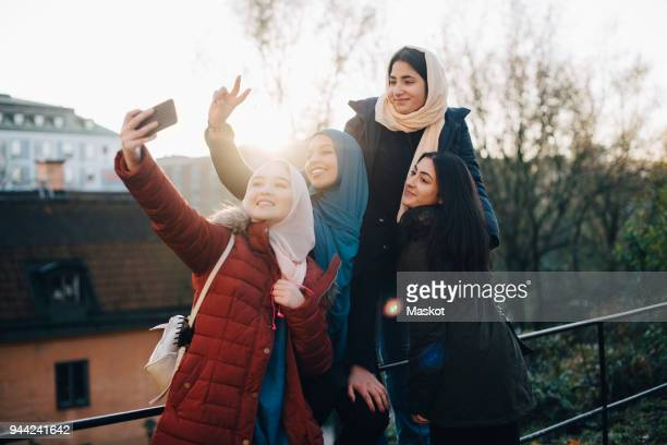 happy young muslim woman taking selfie with friends by railing in city - modest clothing stock pictures, royalty-free photos & images