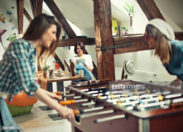 Happy young  office workers playing table football