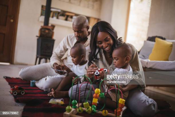 Happy young parents playing with kids and their toys