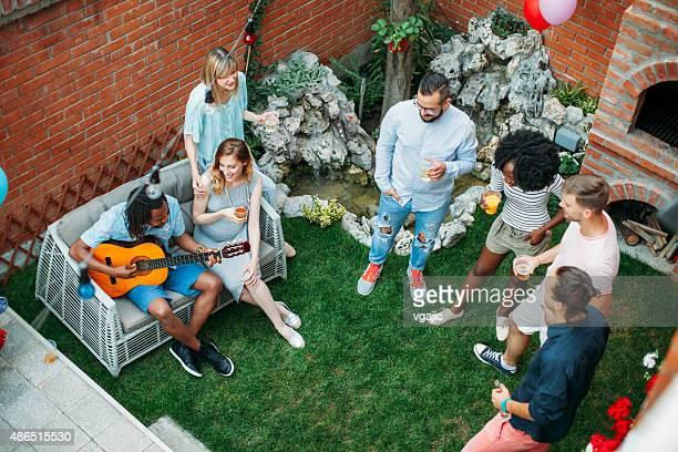 Glückliche junge Menschen tanzen und singen auf Garten-Party.