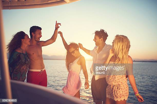 Happy young people dancing on a boat at sunset.