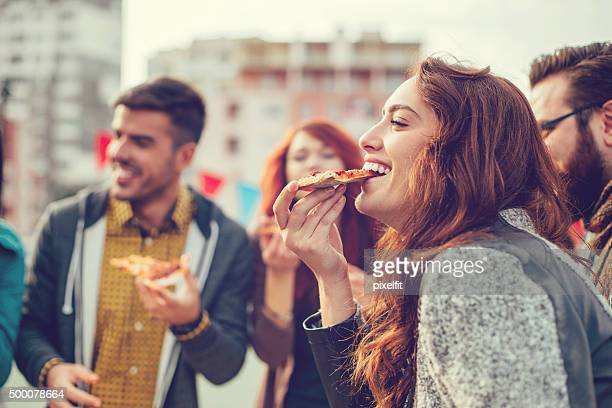 Glückliche junge Menschen Essen pizza im Freien