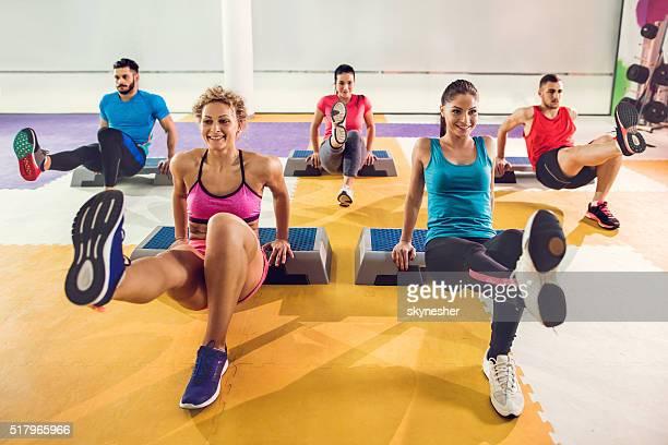 Heureux jeunes ayant pas d'entraînement d'aérobic dans une salle de sport.