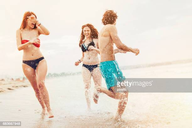 Happy young people playing in the sea