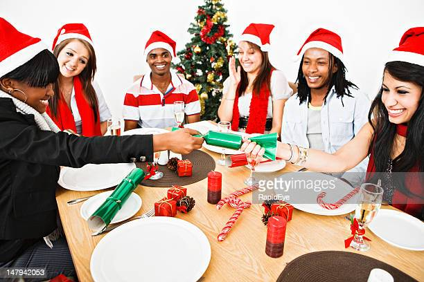 Happy young people pull Christmas crackers at dinner table