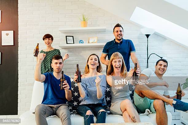 Happy Young People Watching Sport On TV.