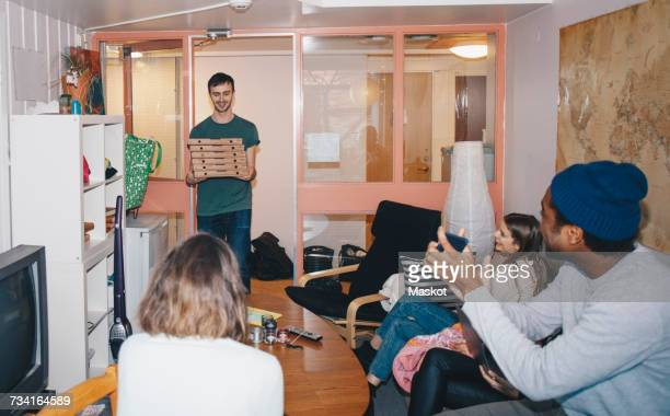 Happy young roommates sitting with man carrying stack of pizza boxes at college dorm