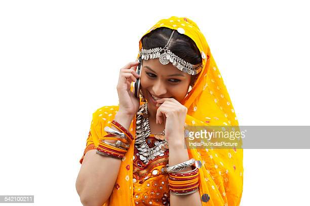 Happy young shy woman using mobile phone over white background