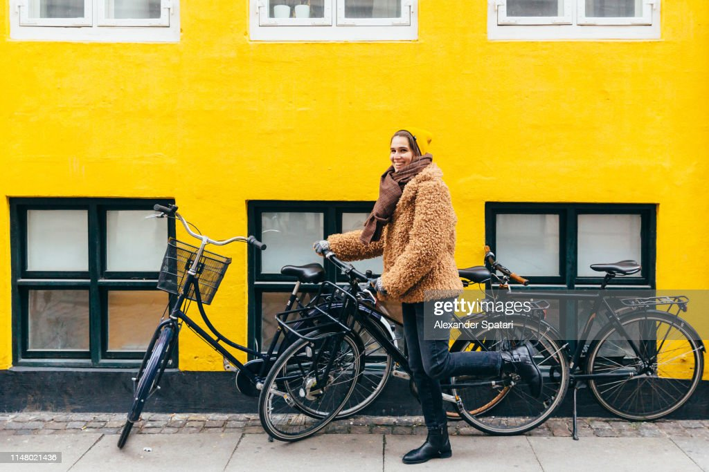Happy young smiling woman with bicycle against yellow wall in Copenhagen : Stock Photo
