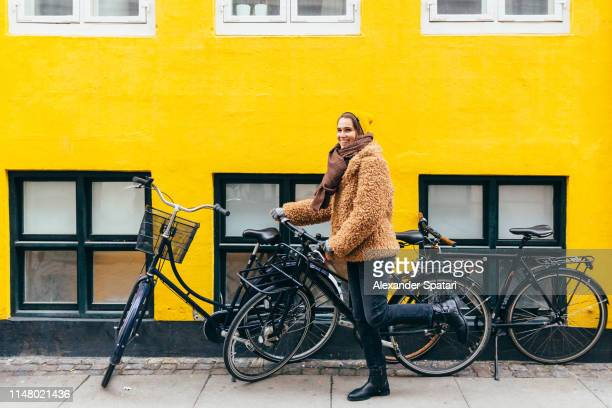 happy young smiling woman with bicycle against yellow wall in copenhagen - copenhague photos et images de collection
