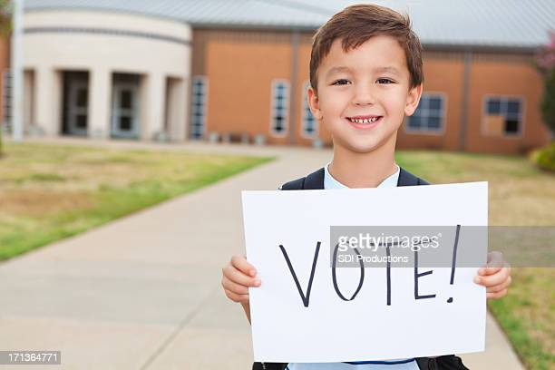 Happy young student at school holding a Vote Sign