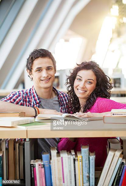 Happy young students studying together at library