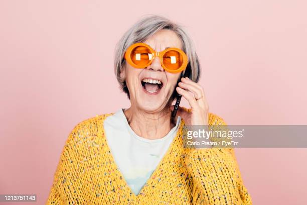 happy young style elderly grandma with orange sunglasses and modern looking laughing on the phone - grandmother stock pictures, royalty-free photos & images