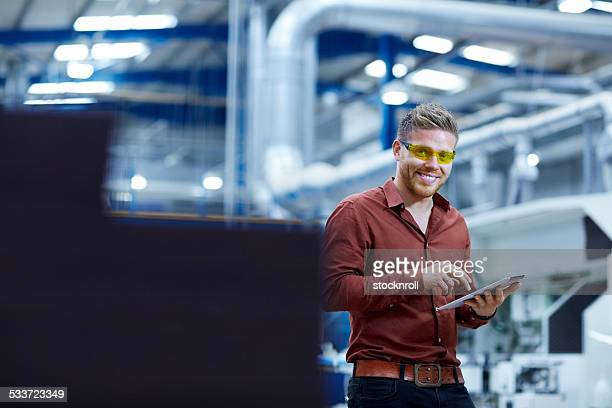 Happy young technician with digital tablet in factory