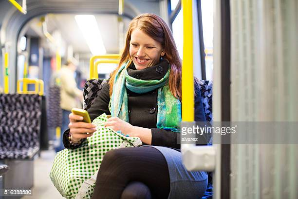 Happy young traveling by subway train using mobile phone