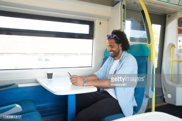 happy young trendy man using smart phone in train - train interior stock pictures, royalty-free photos & images