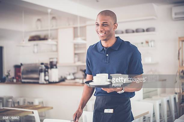 Happy young waiter with coffee cups on tray