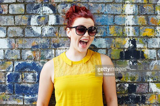 Happy young woman against wall.