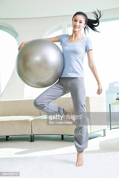 Happy young woman and fitness ball