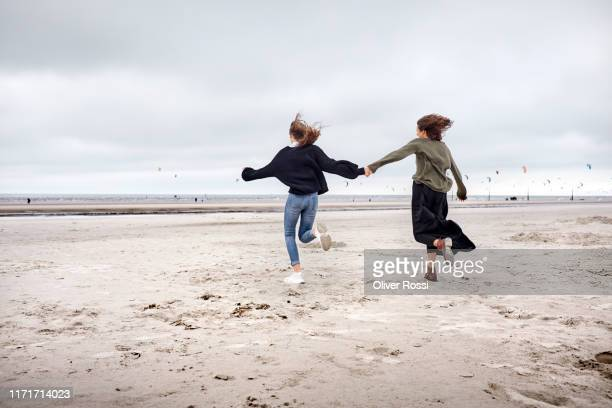 happy young woman and girl running on the beach - schleswig holstein stock pictures, royalty-free photos & images