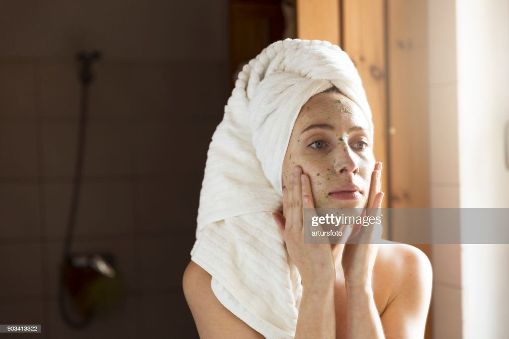 Happy young woman applying face mask in bathroom. Beautiful female in front of mirror doing beauty treatment. : Stock Photo