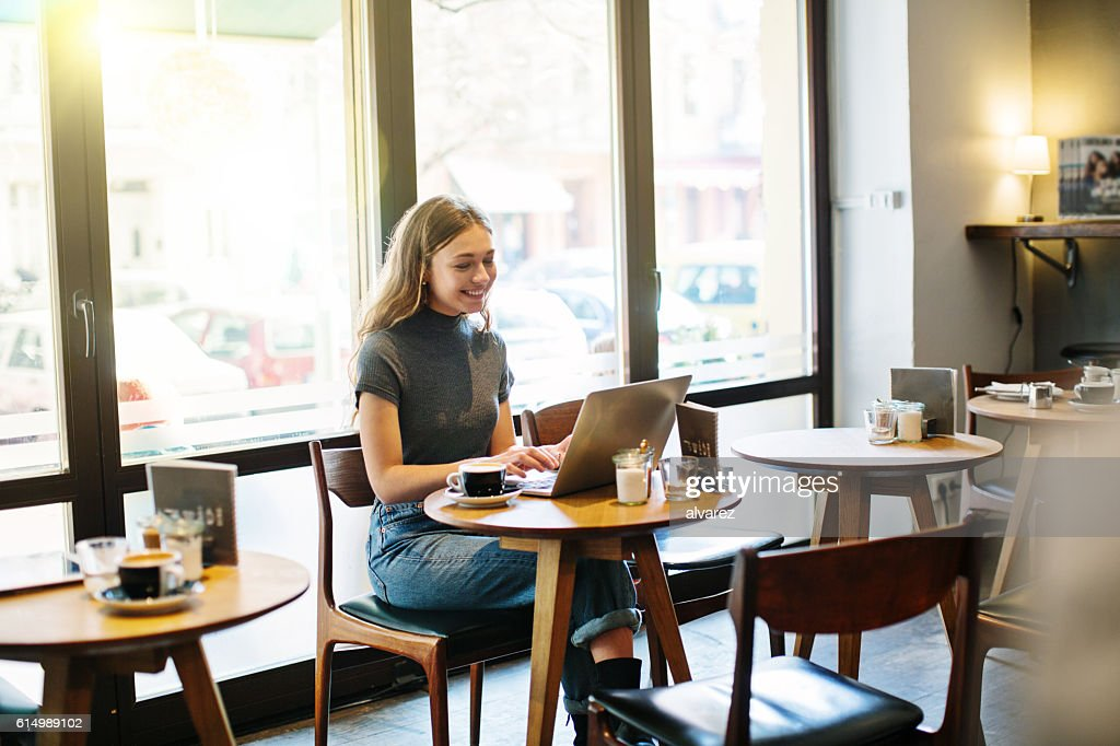 Happy young woman at a cafe using laptop : Stock Photo