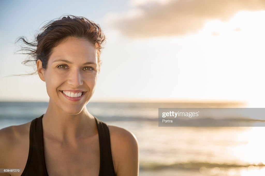 Happy young woman at beach during sunset : Stock Photo